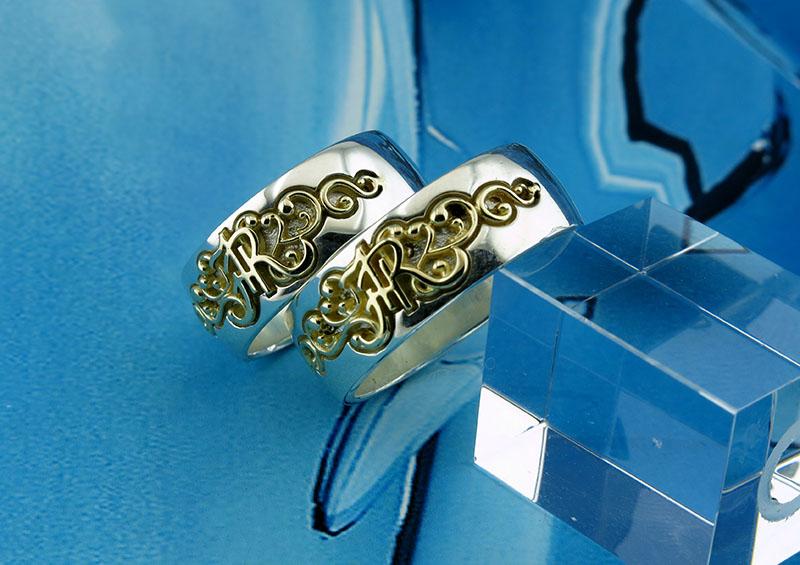 Комплект обручальных колец из серебра с золотыми инициалами.